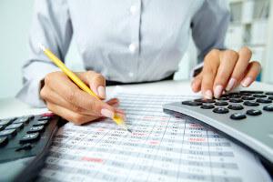 Księgowa z ołówkiem i kalkulatorem podczas prowadzenia księgi przychodów i rozchodów dla klienta